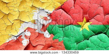 Bhutan flag with Burkina Faso flag on a grunge cracked wall