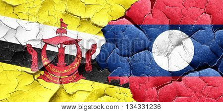 Brunei flag with Laos flag on a grunge cracked wall