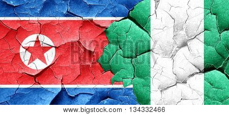 North Korea flag with Nigeria flag on a grunge cracked wall