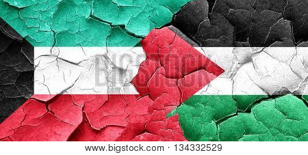 Kuwait flag with Palestine flag on a grunge cracked wall
