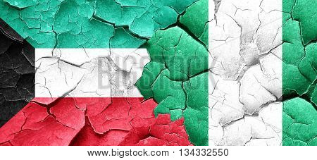 Kuwait flag with Nigeria flag on a grunge cracked wall
