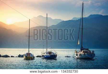 Landscape panorama with sailer boats ships sailing by lake or sea waves in evening sunset sun sunbeams high mountains at background garda veneto region italy
