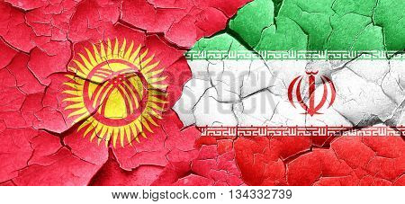 Kyrgyzstan flag with Iran flag on a grunge cracked wall