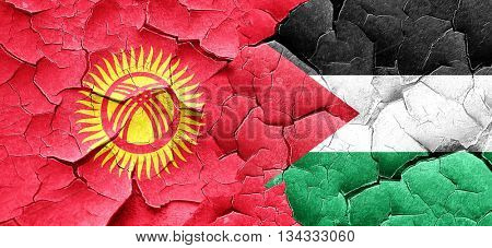 Kyrgyzstan flag with Palestine flag on a grunge cracked wall