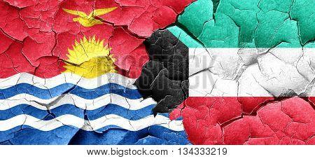 Kiribati flag with Kuwait flag on a grunge cracked wall