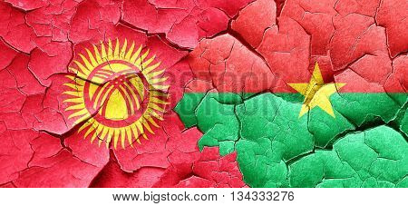 Kyrgyzstan flag with Burkina Faso flag on a grunge cracked wall
