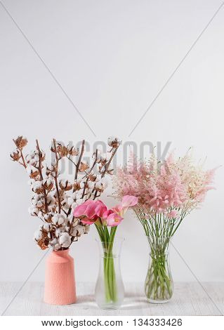 cotton flowers in a vase on a wooden background