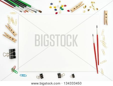 Sketchbook brushes paper office supplies on white background. Artistic flat lay