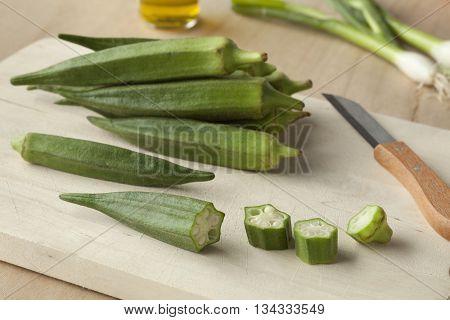 Fresh green okra on a wooden cutting board