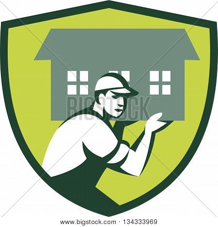 Illustration of a house remover carrying house on shoulder viewed from the side set inside shield crest` done in retro style.