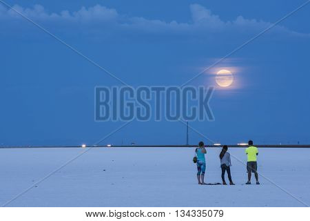 Tooele, USA - August, 29, 2015: White Salt Flats with three people and highway, while supermoon rises