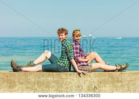 Hiking Couple Relaxing On Sea Coast