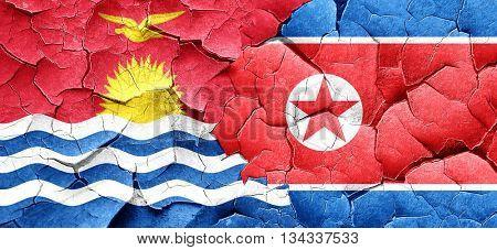 Kiribati flag with North Korea flag on a grunge cracked wall