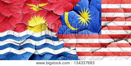 Kiribati flag with Malaysia flag on a grunge cracked wall