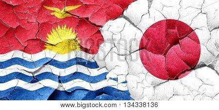 Kiribati flag with Japan flag on a grunge cracked wall