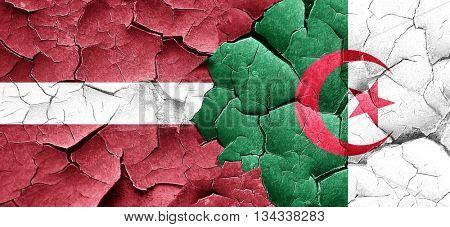 Latvia flag with Algeria flag on a grunge cracked wall