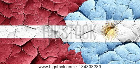 Latvia flag with Argentine flag on a grunge cracked wall