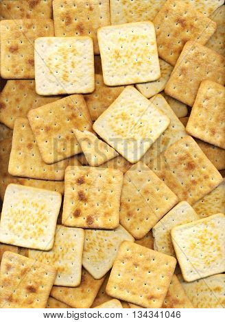 Pile of square salty crackers background. Many baked graham crackers pattern close-up