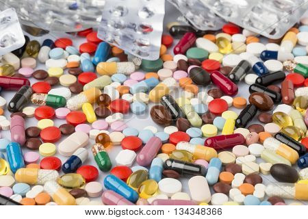 Pharmaceutical background of multi-colored tablets and capsules scattered on the surface