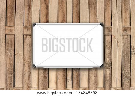 Blank white board on bamboo fence with sepia filter, stock photo