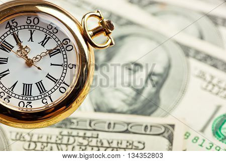 Old clock on background of dollars on the table