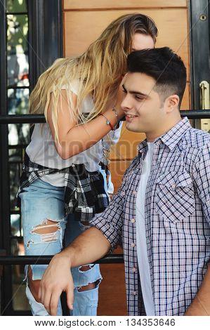 Young beautiful girl whispering to her boyfriend.