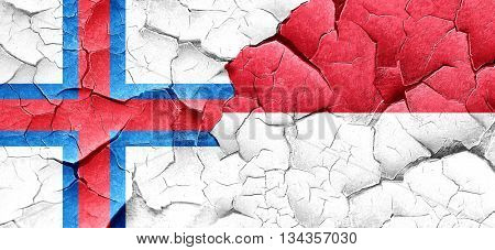 faroe islands flag with Indonesia flag on a grunge cracked wall