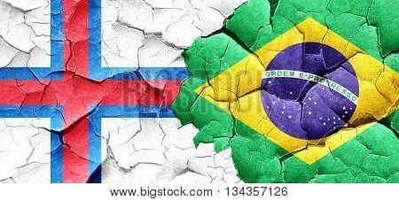 faroe islands flag with Brazil flag on a grunge cracked wall