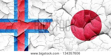 faroe islands flag with Japan flag on a grunge cracked wall