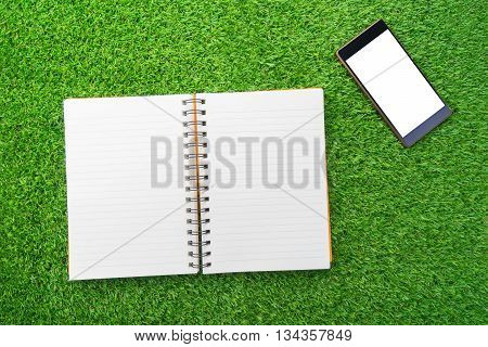 Orange notebook and mobile phone on green grass.