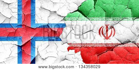 faroe islands flag with Iran flag on a grunge cracked wall