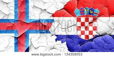 faroe islands flag with Croatia flag on a grunge cracked wall