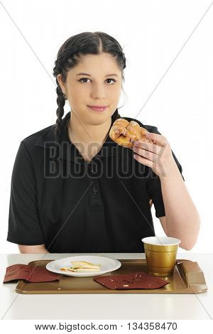 A pretty teen girl looking at the viewer as she's ready to enjoy a glazed fritter, the last of her fast food breakfast.  On a white background.