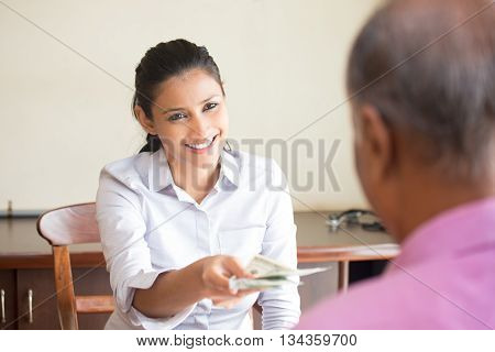 Closeup portrait woman giving cash back refund isolated indoors office background. Excellent customer service with a smile