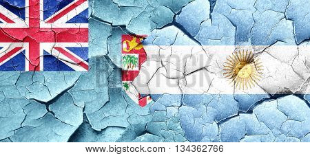 Fiji flag with Argentine flag on a grunge cracked wall
