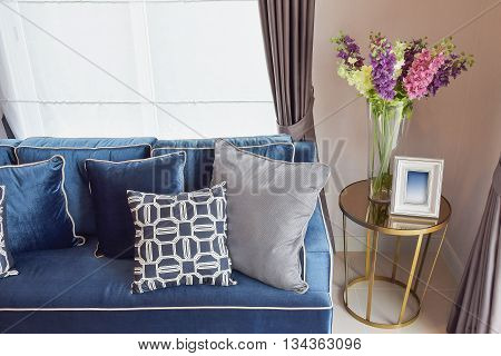 Navy Blue Classic Sofa And Retro Pillows With A Lovely Orchid Vase On Side Table In Living Corner