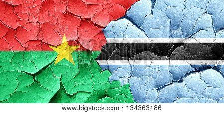 Burkina Faso flag with Botswana flag on a grunge cracked wall