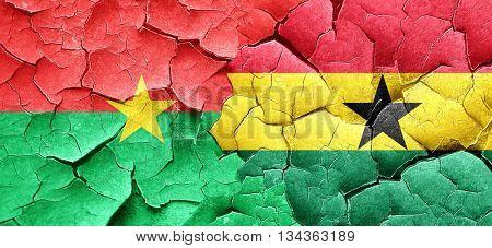 Burkina Faso flag with Ghana flag on a grunge cracked wall