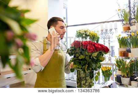 people, sale, retail, business and floristry concept - florist man with red roses calling on smartphone at flower shop counter
