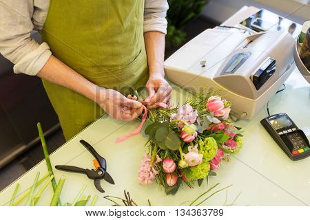people, business, sale and floristry concept - close up of florist man making bunch and tying ribbon at flower shop