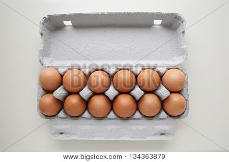Dozen eggs in packaging carton on white table