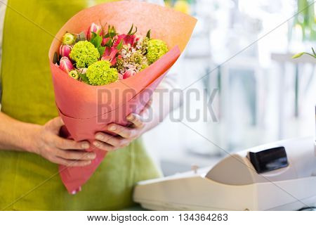 people, shopping, sale, floristry and consumerism concept - close up of florist man holding bunch wrapped in paper at flower shop cashbox