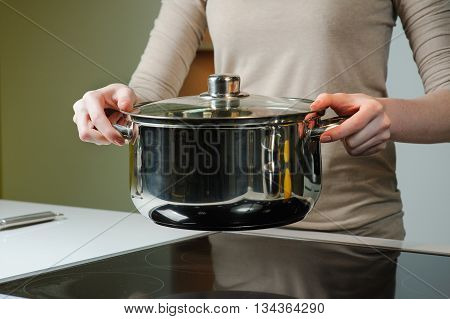 Woman holding a sauce pan in her kitchen. Woman cooks the soup in the kitchen. Close-up of hands holding a pan
