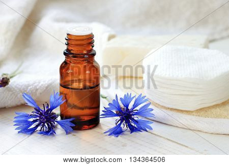 Cornflower herbal tincture. Dark glass apothecary bottle, white towels, cotton pads, fresh blue flowers. Holistic facial skincare. Prevent dark circles.