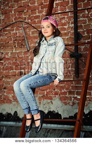 Modern 8 year old girl wearing jeans clothes posing on the city street by a brick wall. Kid's fashion.