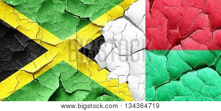 Jamaica flag with Madagascar flag on a grunge cracked wall