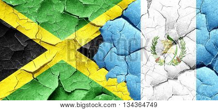 Jamaica flag with Guatemala flag on a grunge cracked wall