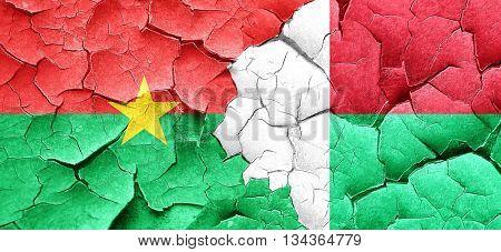 Burkina Faso flag with Madagascar flag on a grunge cracked wall