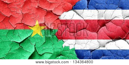 Burkina Faso flag with Costa Rica flag on a grunge cracked wall