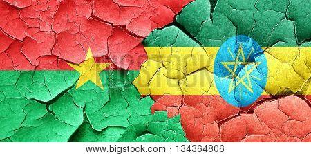 Burkina Faso flag with Ethiopia flag on a grunge cracked wall
